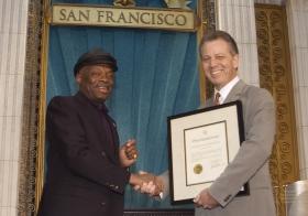 """Para la ocasión, el alcalde de San Francisco Willie Brown (izq.) entregó una proclamación a la Iglesia para encomiarle """"por sus esfuerzos en lograr que Bay Area sea un lugar mejor para las personas de todas las razas, colores, credos y de todo nivel social""""."""